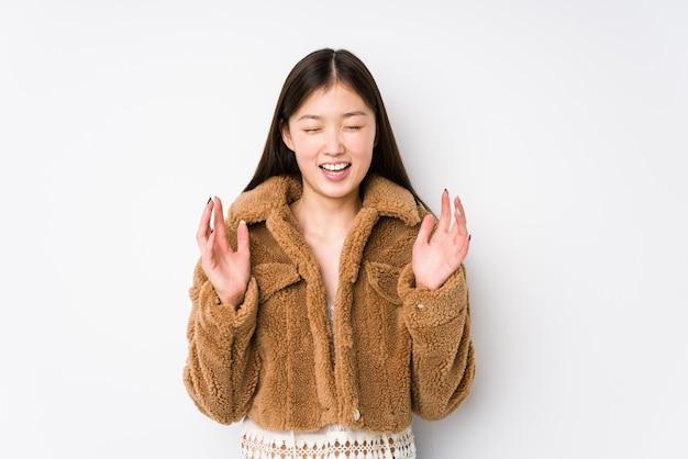 Jovem mulher chinesa posando em um fundo branco isolado alegre rindo muito. conceito de felicidade.