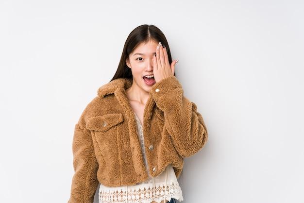 Jovem mulher chinesa posando em um fundo branco isolado se divertindo cobrindo metade do rosto com a palma da mão.