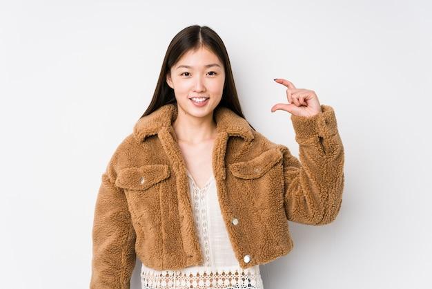 Jovem mulher chinesa posando em um fundo branco isolado segurando algo pequeno com os indicadores, sorrindo e confiante.