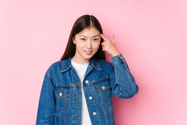 Jovem mulher chinesa posando em um fundo rosa isolado, mostrando um gesto de decepção com o dedo indicador.