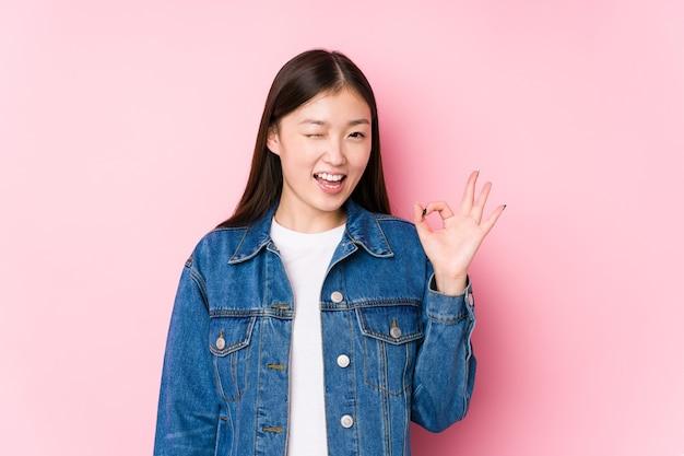 Jovem mulher chinesa posando em um fundo rosa isolado pisca os olhos e segura um gesto de ok com a mão.