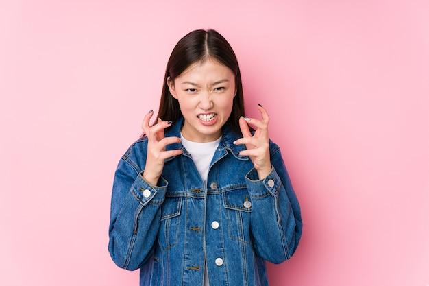 Jovem mulher chinesa posando em uma rosa isolada chateada gritando com as mãos tensas.