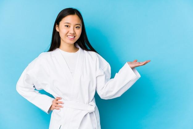 Jovem mulher chinesa praticando karatê, mostrando um espaço de cópia em uma palma e segurando a outra mão na cintura.