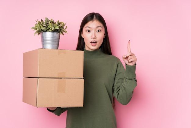 Jovem mulher chinesa segurando caixas isoladas, tendo uma grande ideia, o conceito de criatividade.