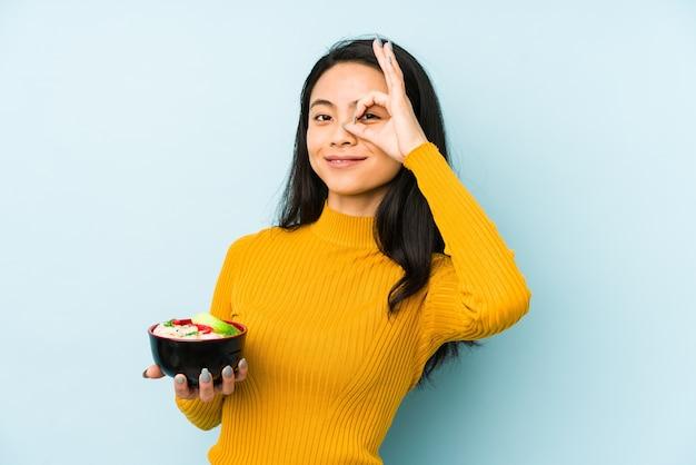 Jovem mulher chinesa segurando macarrão isolado, mantendo um segredo ou pedindo silêncio.