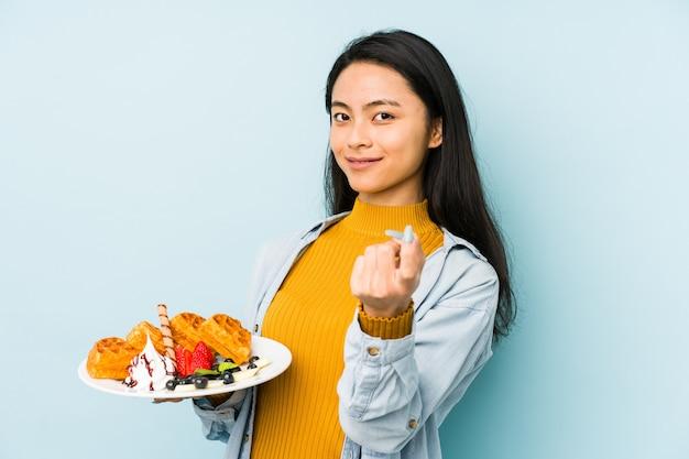 Jovem mulher chinesa segurando waffle na parede azul, tendo uma ideia