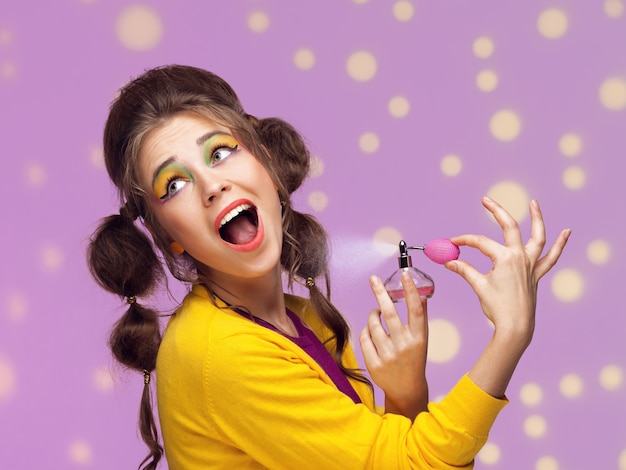 Jovem mulher chique aplicando perfume em parede pontilhada