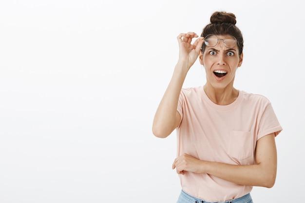 Jovem mulher chocada e ofegante posando contra a parede branca