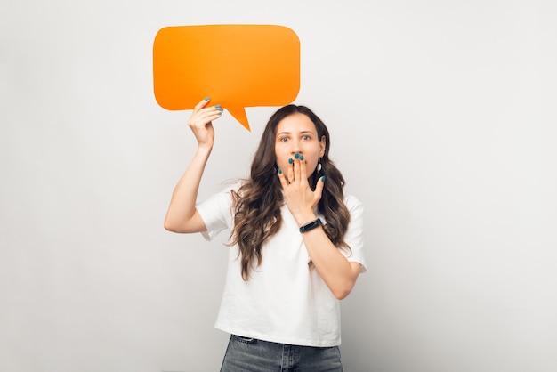 Jovem mulher chocada está segurando um discurso de bolha laranja.