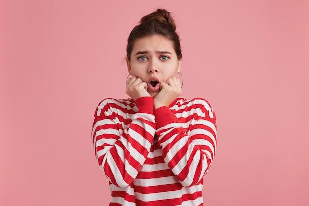 Jovem mulher chocada preocupada, abre a boca segura as mãos perto do rosto e morde as unhas abertas