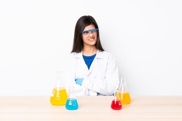 Jovem mulher científica em uma mesa com confundir a expressão do rosto