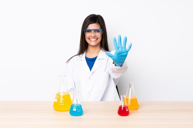 Jovem mulher científica em uma mesa contando cinco com os dedos
