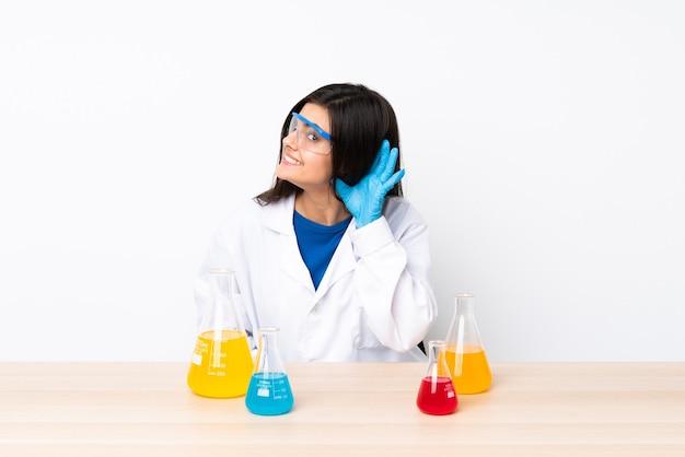 Jovem mulher científica em uma mesa ouvindo algo colocando a mão no ouvido