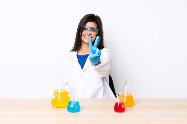 Jovem mulher científica em uma mesa, sorrindo e mostrando sinal de vitória