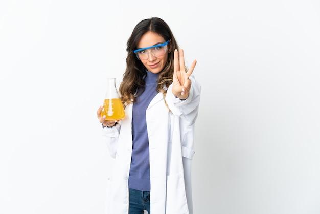 Jovem mulher científica isolada na parede branca feliz e contando três com os dedos