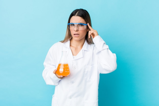 Jovem mulher científica mostrando um gesto de decepção com o dedo indicador.