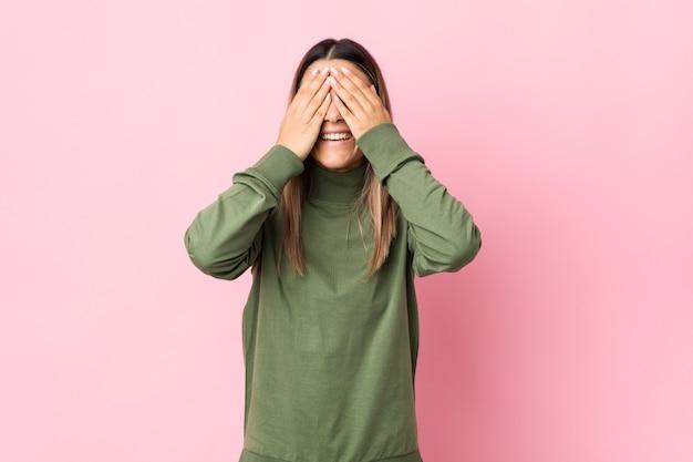 Jovem mulher cobre os olhos com as mãos, sorri amplamente à espera de uma surpresa
