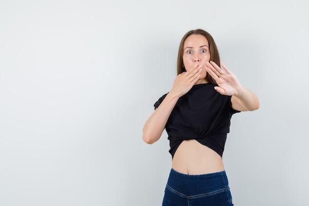 Jovem mulher cobrindo a boca com a mão enquanto mostra o gesto de parada na blusa preta e parece preocupada.