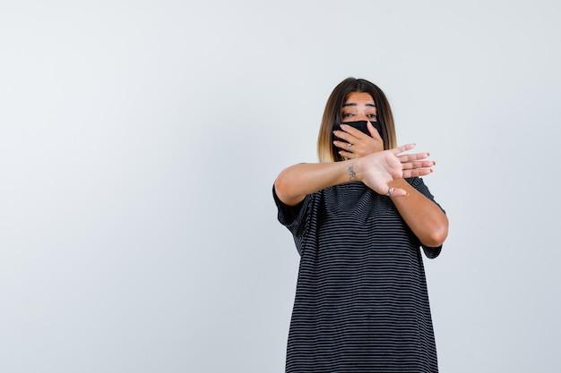 Jovem mulher cobrindo a boca com a mão, mostrando o sinal de pare em um vestido preto, máscara preta e parecendo assustado, vista frontal.
