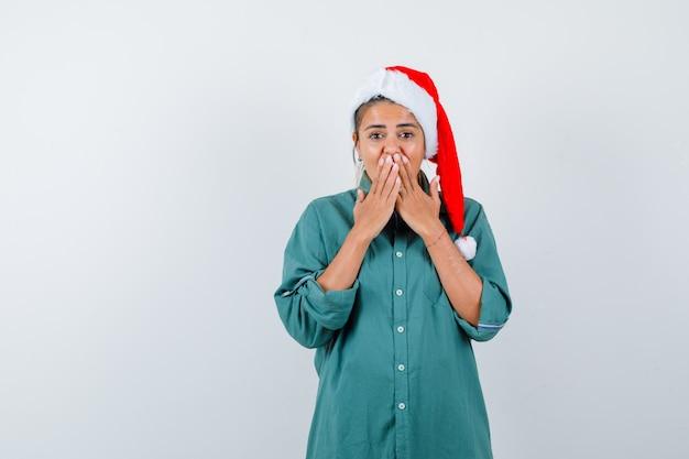 Jovem mulher cobrindo a boca com as mãos na camisa, chapéu de papai noel e olhando atônito, vista frontal.