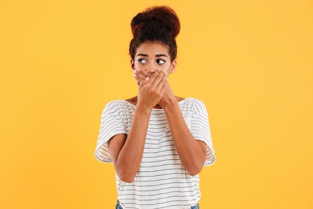 Jovem mulher cobrindo a boca isolada