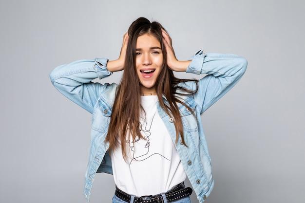 Jovem mulher cobrindo as orelhas e gritando isolado em uma parede branca