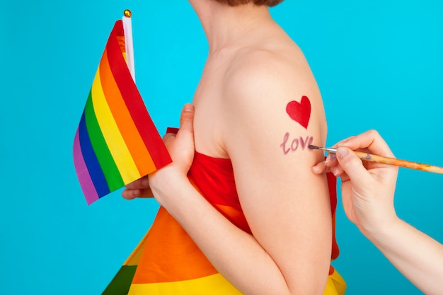 Jovem mulher cobrindo com bandeira do orgulho lgbt