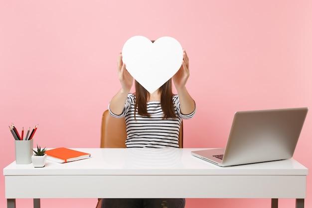 Jovem mulher cobrindo o rosto com um coração branco com espaço de cópia, trabalhando no projeto enquanto está sentado no escritório com o laptop isolado no fundo rosa pastel. conceito de carreira empresarial de realização. área de publicidade.
