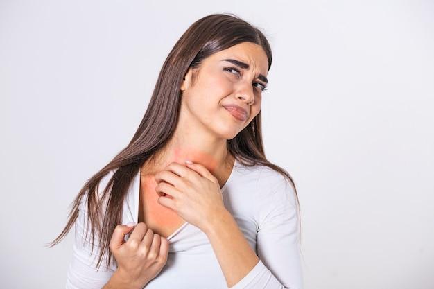 Jovem mulher coçando o pescoço devido a coceira em um fundo cinza. a mulher tem coceira no pescoço. o conceito de sintomas de alergia e cuidados de saúde