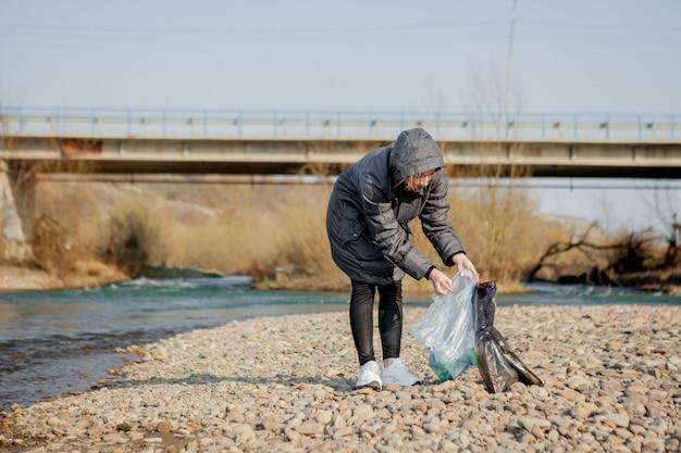 Jovem mulher coletando lixo plástico da praia e colocando-o em sacos de plástico pretos para reciclagem