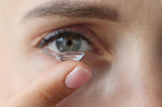Jovem mulher colocando lentes de contato, seleção de conceito de lentes de contato