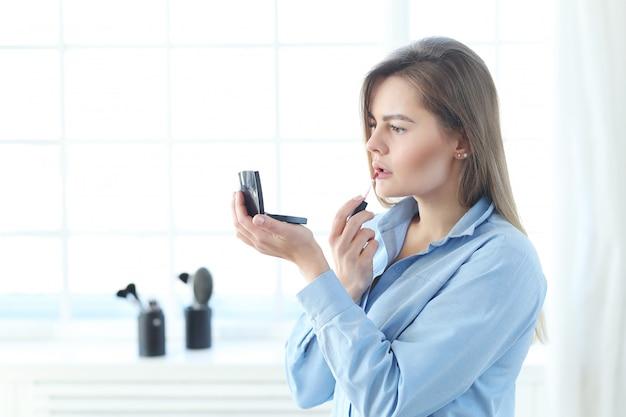 Jovem mulher colocando maquiagem.
