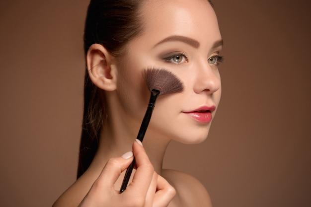 Jovem mulher colocando maquiagem