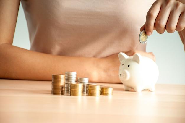 Jovem mulher colocando moedas em um cofrinho