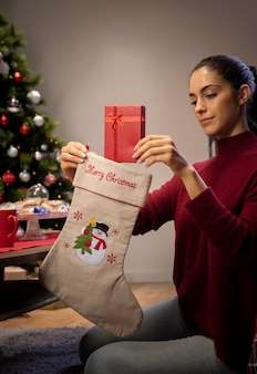 Jovem mulher colocando presentes em meias gigantes