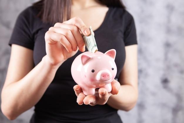 Jovem mulher colocando uma moeda dentro do cofrinho como poupança para investimento