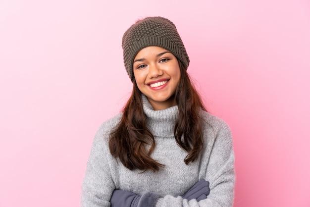 Jovem mulher colombiana com chapéu de inverno sobre parede rosa isolada rindo