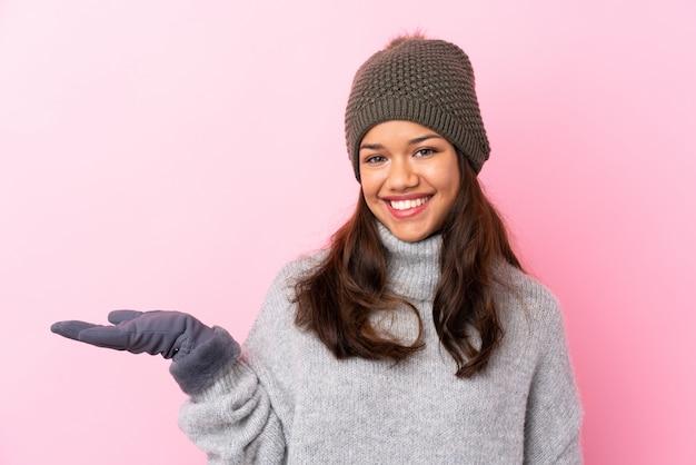 Jovem mulher colombiana com chapéu de inverno sobre parede rosa isolada segurando copyspace imaginário na palma da mão