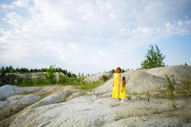 Jovem mulher com a filha em um vestido amarelo perto do lago com água azul e árvores verdes. conceito de relacionamento familiar feliz