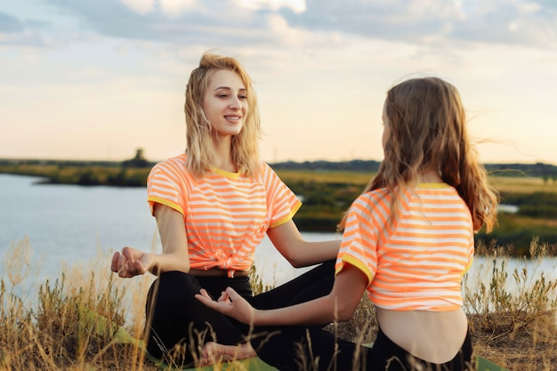 Jovem mulher com a filha fazendo ioga ao ar livre