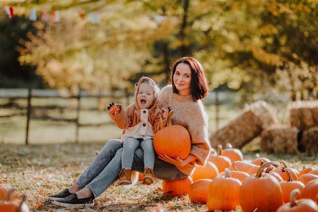 Jovem mulher com a filha sentada sobre abóboras