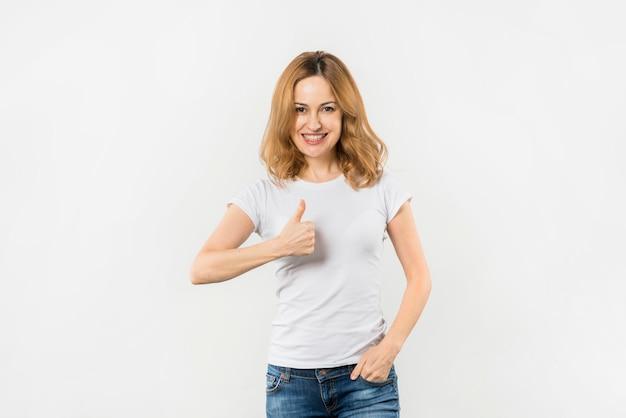 Jovem mulher com a mão no bolso, mostrando o polegar para cima o sinal