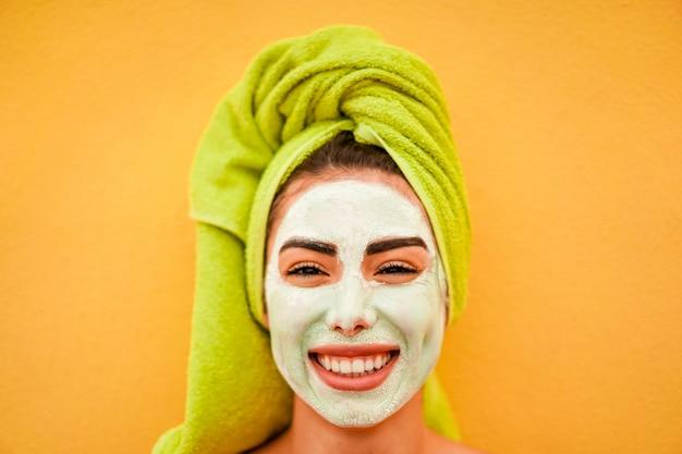 Jovem mulher com a máscara natural da beleza que está sobre o fundo amarelo - cuidados com a pele, estilo de vida saudável e conceito da loja de cosméticos - foco no nariz