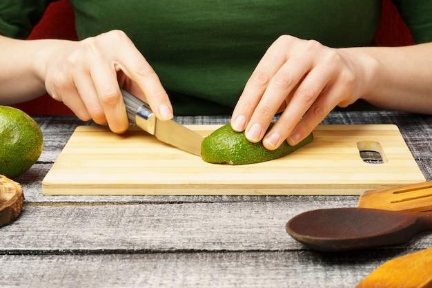 Jovem mulher com abacate fresco à mesa. a garota corta o abacate. o processo de preparação de alimentos saudáveis