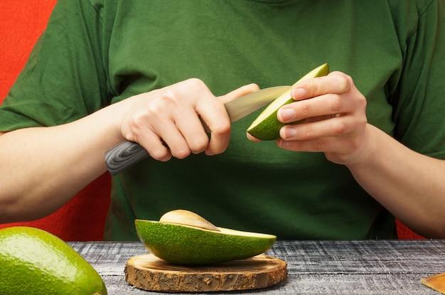 Jovem mulher com abacate fresco à mesa. a menina está limpando um abacate verde. o processo de preparação de alimentos saudáveis
