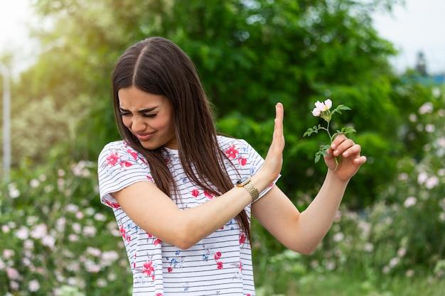 Jovem mulher com alergia ao pólen, segurando uma flor e dizendo não.