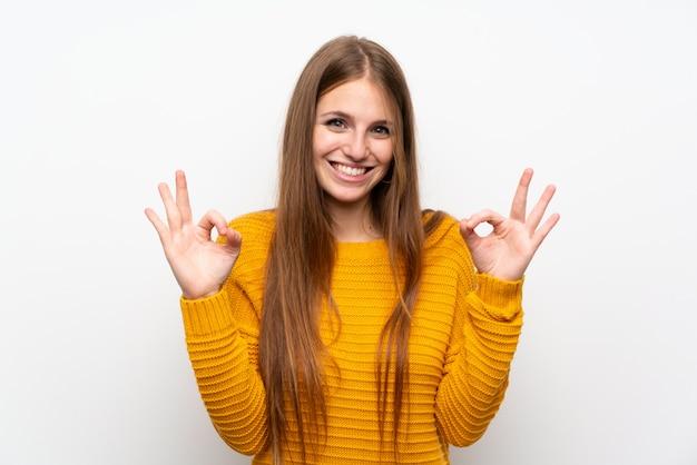 Jovem mulher com amarelo sobre parede branca isolada, mostrando um sinal de ok com os dedos