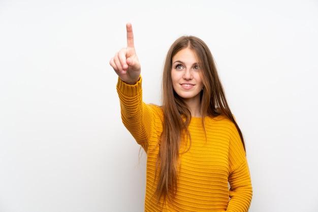Jovem mulher com amarelo sobre parede branca isolada tocando na tela transparente