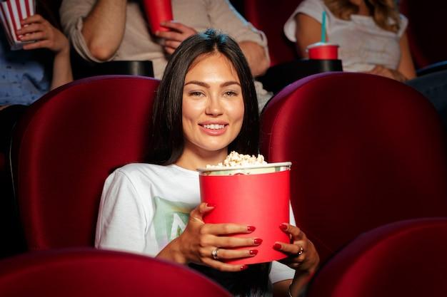 Jovem mulher com amigos assistindo filme no cinema