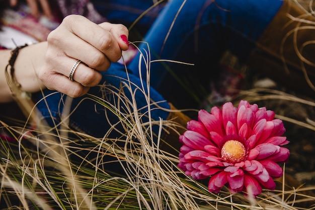 Jovem mulher com anel na mão descansando na grama perto de uma flor-de-rosa.